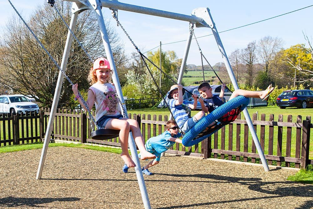 Children using the new swings on the play park.